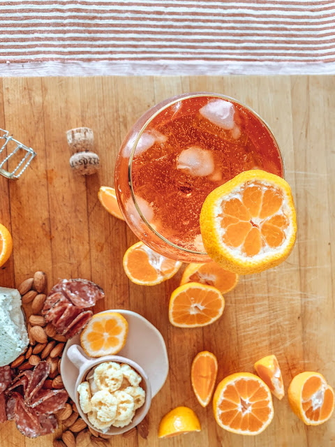 A freshly made aperol sprit on a charcuterie board with meat, nuts, cheese and oranges
