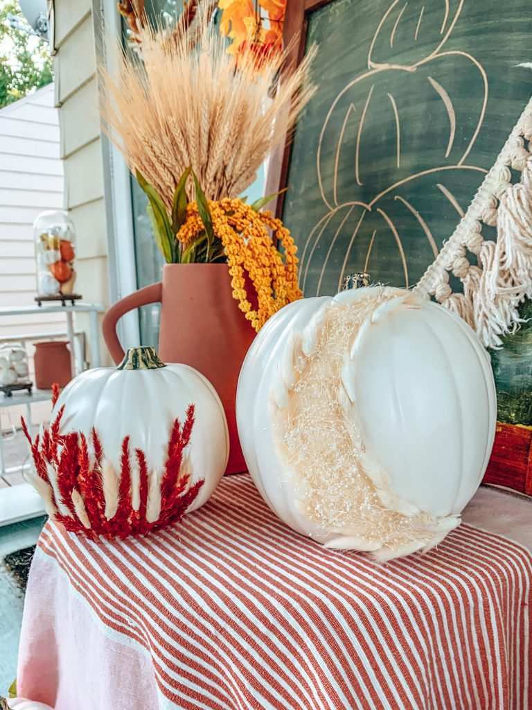 Fall pumpkins decorated with dried florals on front porch